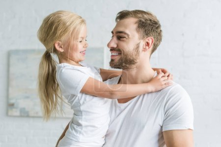Photo for Happy father and cute little daughter hugging and smiling each other at home - Royalty Free Image