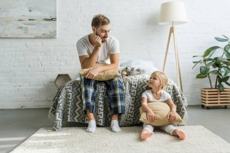 Photo for Father in pajamas sitting on bed and looking at cute little daughter sitting with pillow on carpet - Royalty Free Image