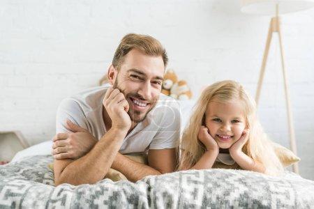 Photo pour Heureux père et mignonne petite fille couché ensemble sur lit et souriant à la caméra - image libre de droit
