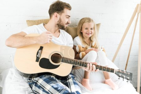 Photo for Happy father with acoustic guitar looking at cute little daughter with teddy bear on bed - Royalty Free Image