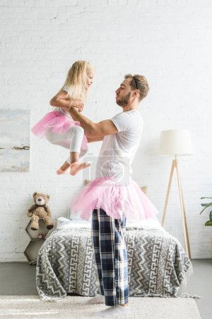side view of happy father and cute little daughter in pink tutu skirts dancing at home