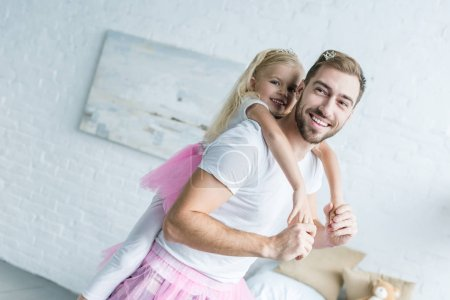 adorable little daughter in pink tutu skirt hugging happy father at home