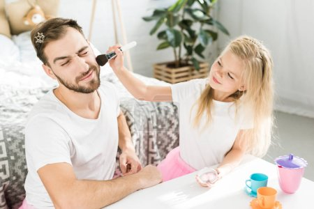 Photo for Smiling little daughter applying makeup to bearded father at home - Royalty Free Image