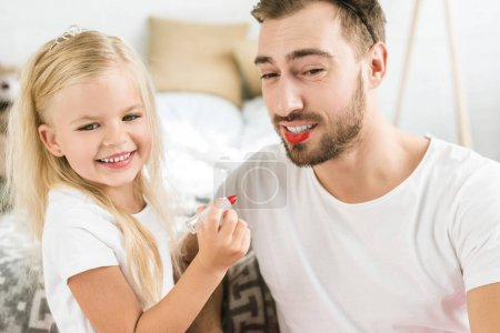 happy father and cute little daughter playing and applying makeup at home