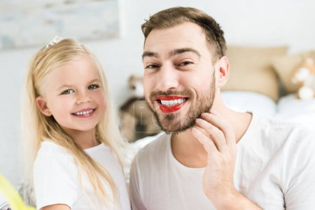 adorable little daughter and happy bearded father with red lipstick smiling at camera