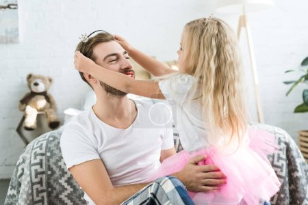 cute little daughter in pink tutu skirt wearing headband with crown to happy father