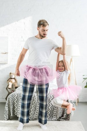 father and adorable little daughter in pink tutu skirts having fun at home