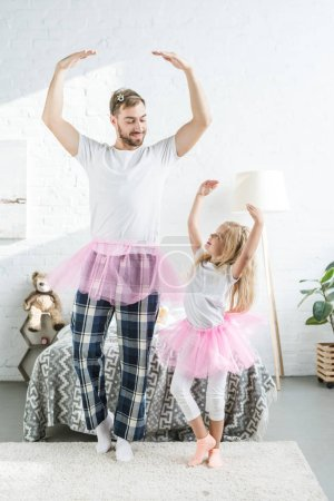 happy father and adorable little daughter in pink tutu skirts dancing and smiling each other
