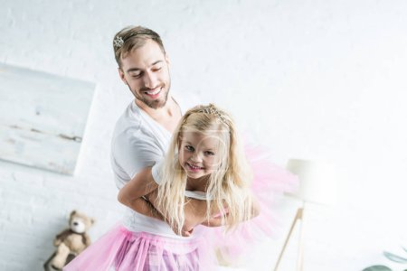 happy father and adorable little daughter in pink tutu skirts dancing at home