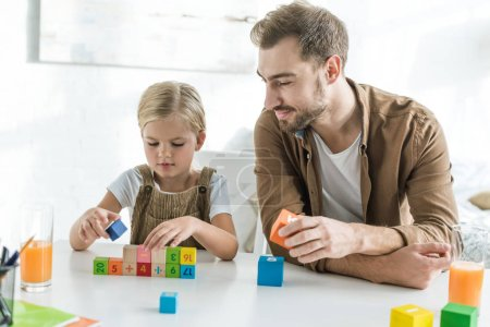 smiling father looking at cute little daughter playing with colorful cubes at home