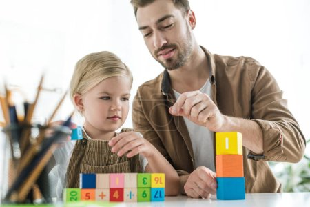father explaining math to little daughter and playing with colorful cubes at home