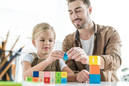 happy father and adorable little daughter learning math with colorful cubes at home