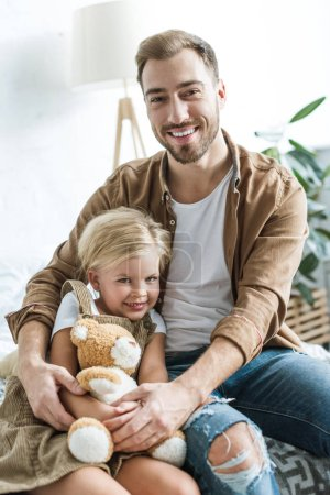 happy father and daughter with teddy bear sitting together at home