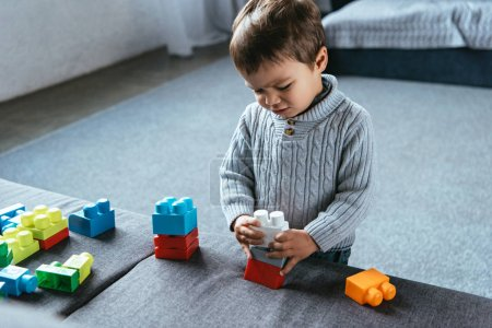 irritated little boy playing with colorful plastic blocks at home