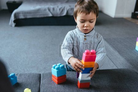 Photo for Focused little boy playing with colorful plastic blocks at home - Royalty Free Image