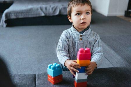 Photo pour Foyer sélectif de petit garçon jouant avec des blocs en plastique colorés à la maison - image libre de droit