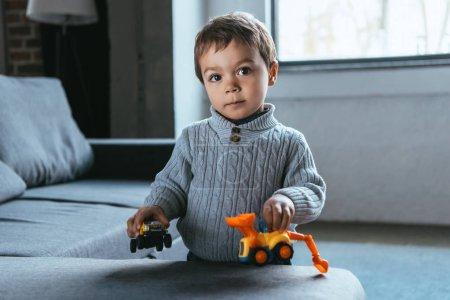Foto de Niño alegre jugando con coches de juguete en la sala de estar en casa - Imagen libre de derechos
