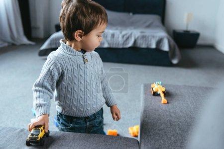 Photo pour Foyer sélectif de garçon jouant avec des voitures jouet dans le salon à la maison - image libre de droit