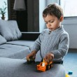 Cute boy playing with toy cars in living room at h...