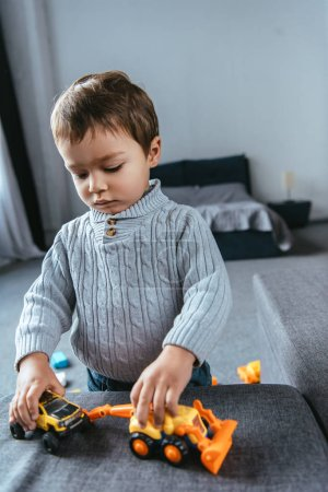 selective focus of boy playing with toy cars in living room at home