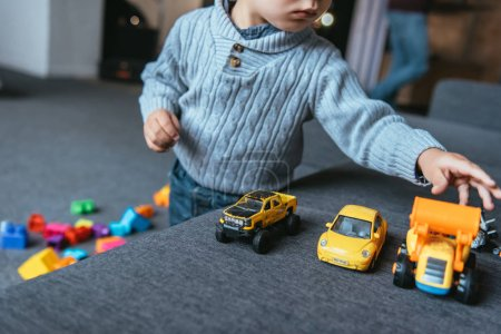 partial view of boy playing with toy cars in living room at home