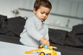 little boy playing with toy cars in living room at home