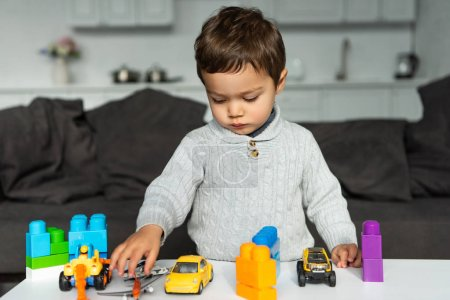 Foto de Enfoque selectivo de niño jugando con coches de juguete y bloques de en mesa de salón en casa - Imagen libre de derechos