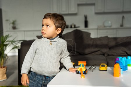kid playing with toy cars at table in living room at home