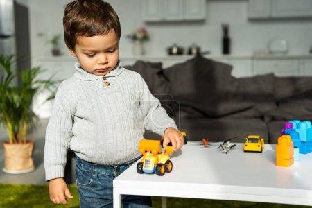 Foto de Niño jugando con coches de juguete en mesa de salón en casa - Imagen libre de derechos