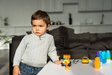 serious playing with toy cars at table in living room at home