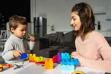 Photo for Little boy and his mother playing with colorful plastic blocks at home - Royalty Free Image