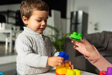 Photo pour Image recadrée de la femme jouant blocs en plastique avec petit fils à la maison - image libre de droit
