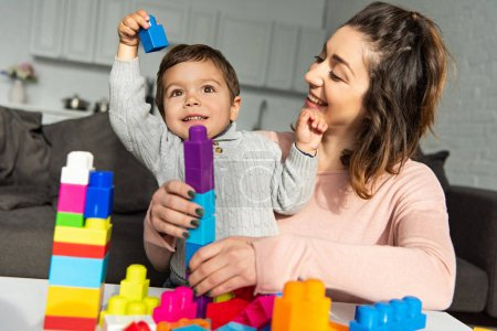 Photo for Adorable boy and his mother playing with colorful plastic blocks at home - Royalty Free Image