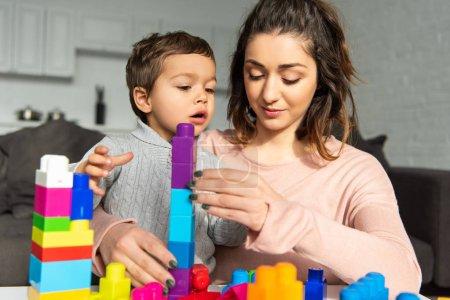 Photo pour Mignon garçon et sa mère jouer avec des blocs en plastique coloré à la maison - image libre de droit
