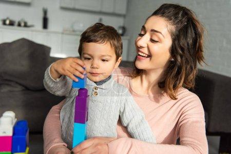 Foto de Niño alegre y su madre jugando con bloques de colores en casa - Imagen libre de derechos