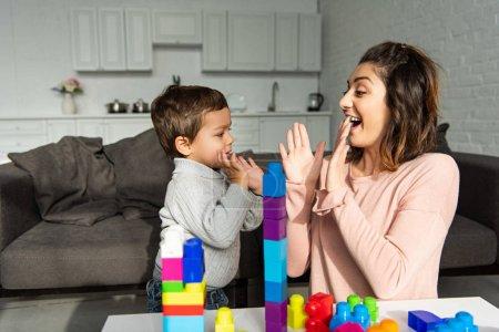 Photo pour Femme gaie faisant pat-a-cake avec petit fils à la maison - image libre de droit