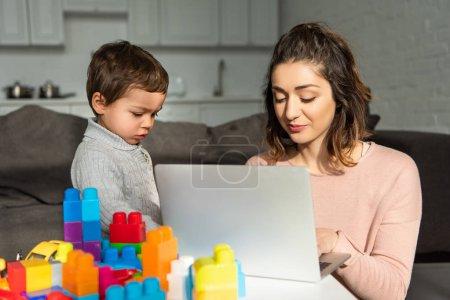 entzückende kleine Junge und seine Mutter mit Laptop am Tisch im Wohnzimmer zu Hause