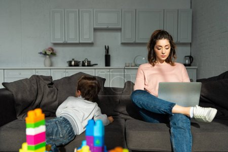 Photo for Rear view of little boy climbing on sofa while his mother using laptop at home - Royalty Free Image