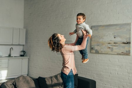side view of laughing woman raising happy little son in living room at home