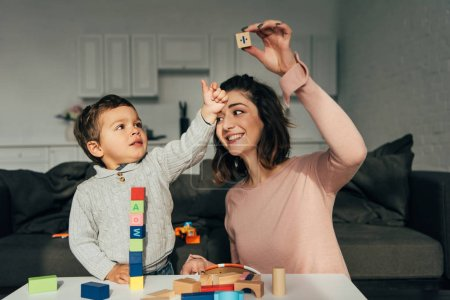 Photo for Kid and his mother playing blocks wood tower game at home - Royalty Free Image