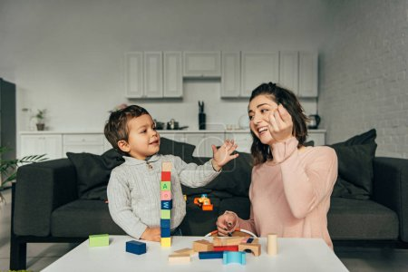Photo for Smiling little boy and his mother playing blocks wood tower game at home - Royalty Free Image