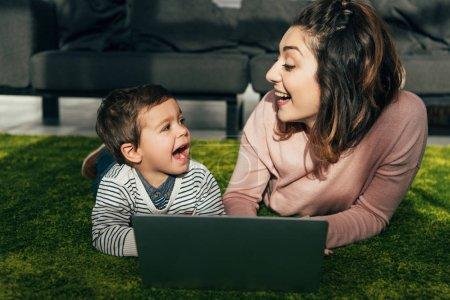 Photo pour Rire la mère et le petit fils regardent tout en jetant sur le plancher avec l'ordinateur portable à la maison - image libre de droit