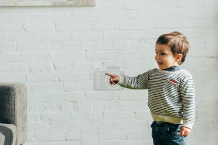 Photo for Smiling little child pointing by finger in living room at home - Royalty Free Image