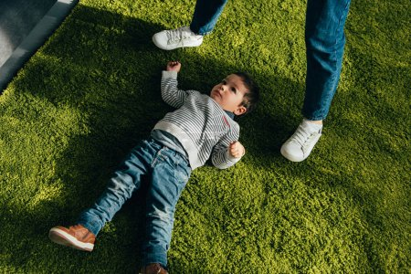 Photo for Cropped image of mother standing above little son laying on floor at home - Royalty Free Image