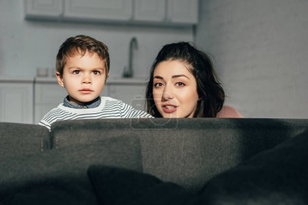 portrait of mother and little son sitting on sofa at home