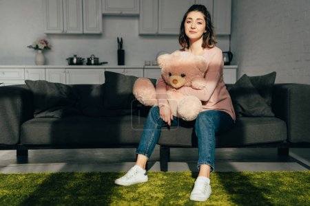 beautiful woman sitting on sofa with pink teddy bear in living room at home