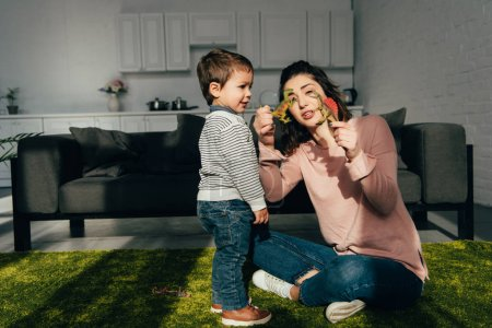 attractive mother showing toy dinosaurs to her little son in living room at home