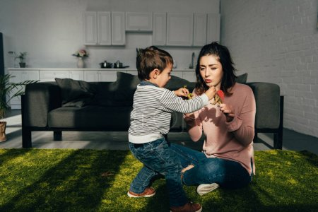 mother and little son playing toy dinosaurs in living room at home
