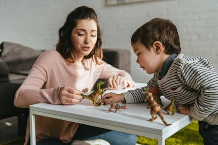 cheerful woman and little son playing toy dinosaurs at table in living room at home