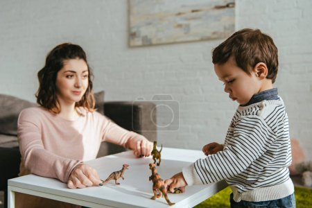 selective focus of mother and little son playing toy dinosaurs at table in living room at home
